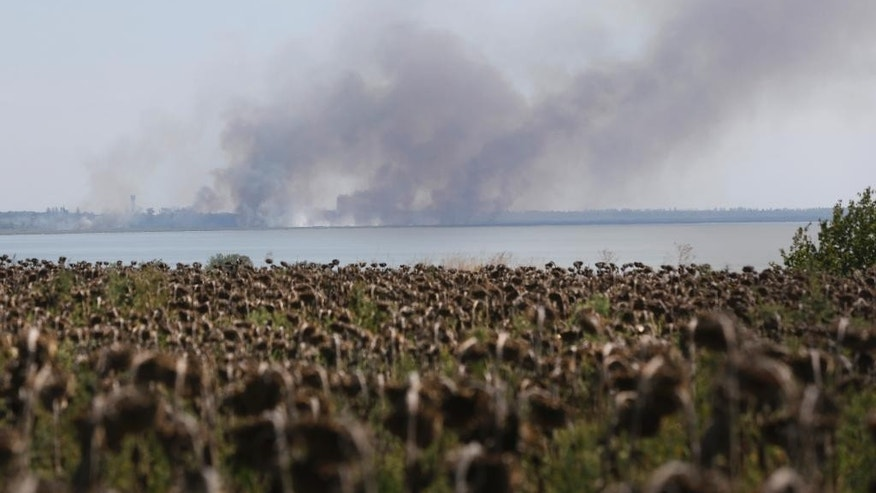 Aug. 26, 2014: Smoke rises after shelling in the town of Novoazovsk, eastern Ukraine. Towering columns of smoke rose Tuesday from outside a city in Ukraine's far southeast after what residents said was a heavy artillery barrage.