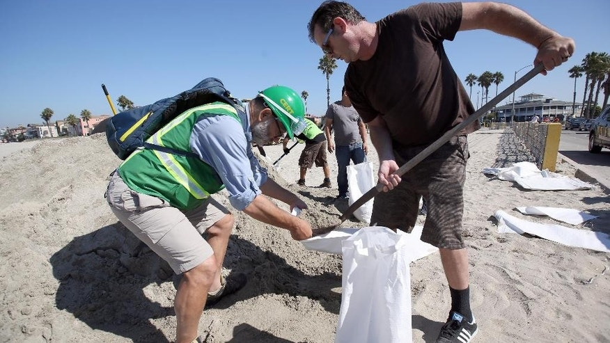 Community volunteer Edwin Schakeroh, left, helps Gavin Greely a resident fill sand bags in preparing for an expected storm surge in Long Beach, Calif., Tuesday, Aug. 26, 2014. Southern California coastal areas are preparing for the arrival of big and potentially damaging surf spawned by Hurricane Marie spinning off Mexico's Pacific coast. (AP Photo/ Nick Ut )