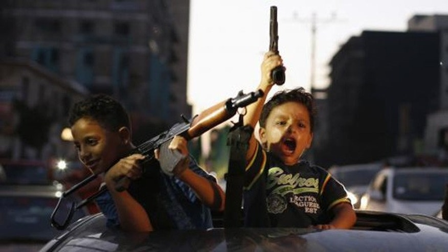 August 26, 2014: Palestinian children hold guns as they celebrate what Hamas claimed was a victory over Israel, following a ceasefire in Gaza City. (Reuters/SUHAIB SALEM)