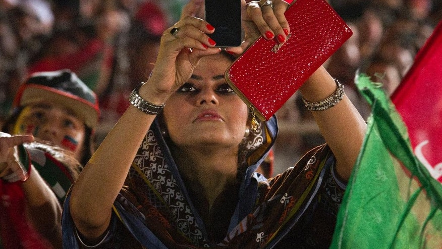 A supporter of Pakistan's cricketer-turned-politician Imran Khan uses her cell phone to take picture of Khan during a protest near the parliament building in Islamabad, Pakistan, Monday, Aug. 25, 2014.  Thousands of supporters of Pakistan's cricketer-turned-politician Imran Khan and Muslim cleric Tahir-ul-Qadri are besieging parliament in the capital to pressure Sharif to resign over alleged election fraud. (AP Photo/Anjum Naveed)