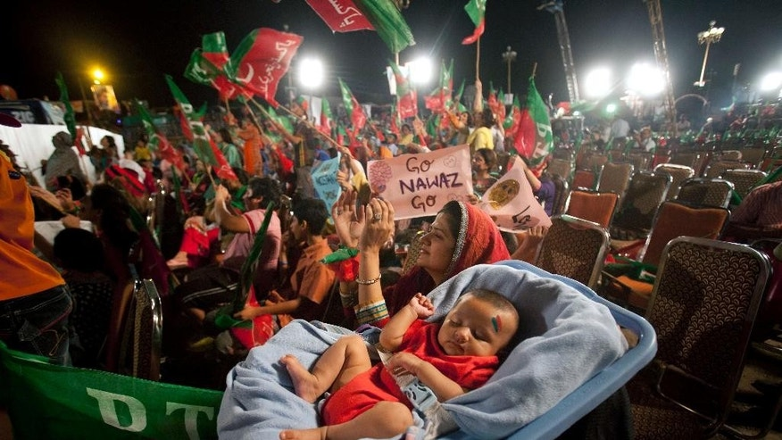 A child sleeps as her mother claps during a protest staged by Pakistan's cricketer-turned-politician Imran Khan near the parliament building in Islamabad, Pakistan, Monday, Aug. 25, 2014. Thousands of supporters of Pakistan's cricketer-turned-politician Imran Khan and Muslim cleric Tahir-ul-Qadri are besieging parliament in the capital to pressure Sharif to resign over alleged election fraud. (AP Photo/Anjum Naveed)