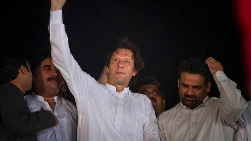 Pakistan's cricketer-turned-politician Imran Khan, center, gestures to his supporters during a protest near the parliament building in Islamabad, Pakistan, Monday, Aug. 25, 2014. Thousands of supporters of Pakistan's cricketer-turned-politician Imran Khan and Muslim cleric Tahir-ul-Qadri are besieging parliament in the capital to pressure Sharif to resign over alleged election fraud. (AP Photo/Anjum Naveed)