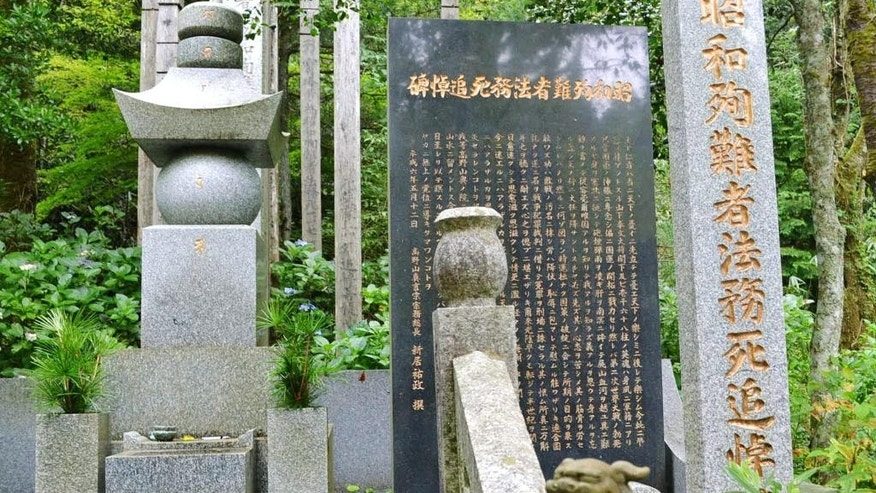 A stone-carved guardian dog sits in front of a memorial compound honoring World War II-era war criminals in Koyasan Okuno-in temple in Koya town, Wakayama prefecture, central Japan, Wednesday, Aug. 27, 2014. Japan's Chief Cabinet Secretary Yoshihide Suga acknowledged Wednesday that Prime Minister Shinzo Abe on April 29 sent a note to the Koyasan temple's ceremony honoring hundreds of war criminals that praised their contributions to the country. Suga said that Abe sent the note to the ceremony, but in his capacity as head of the ruling Liberal Democratic Party, not as prime minister. (AP Photo/Kyodo News) JAPAN OUT, CREDIT MANDATORY