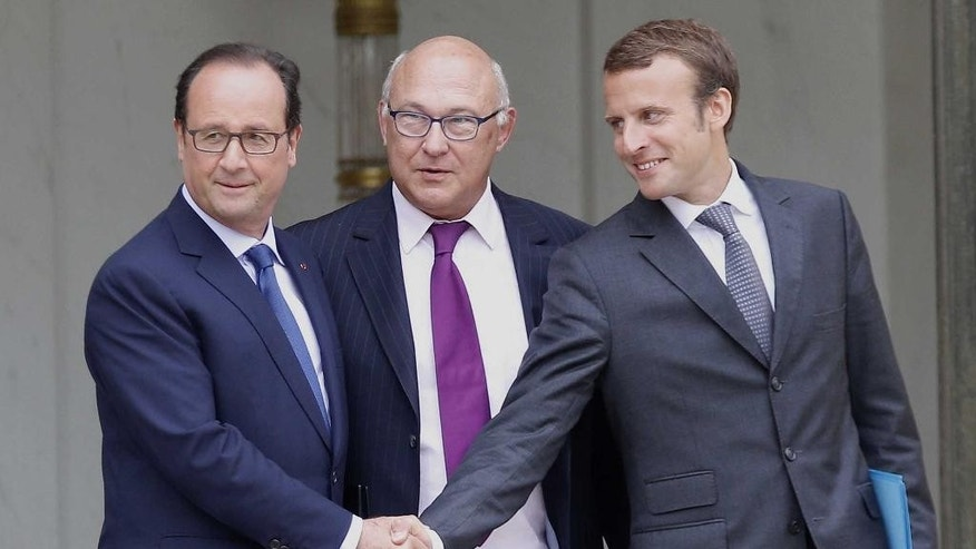 France's President Francois Holland, left, shakes hands with France's new Economy Minister Emmanuel Macron, right, as French finance minister Michel Sapin, centre, looks on,  as they leave their weekly cabinet meeting, in Paris, Wednesday, Aug. 27, 2014. France's prime minister reshuffled his Cabinet on Tuesday to silence ministers who had openly criticized Socialist President Francois Hollande's economic policies as he tries to pull the nation out of stagnation and steer it toward growth. (AP Photo/Christophe Ena)