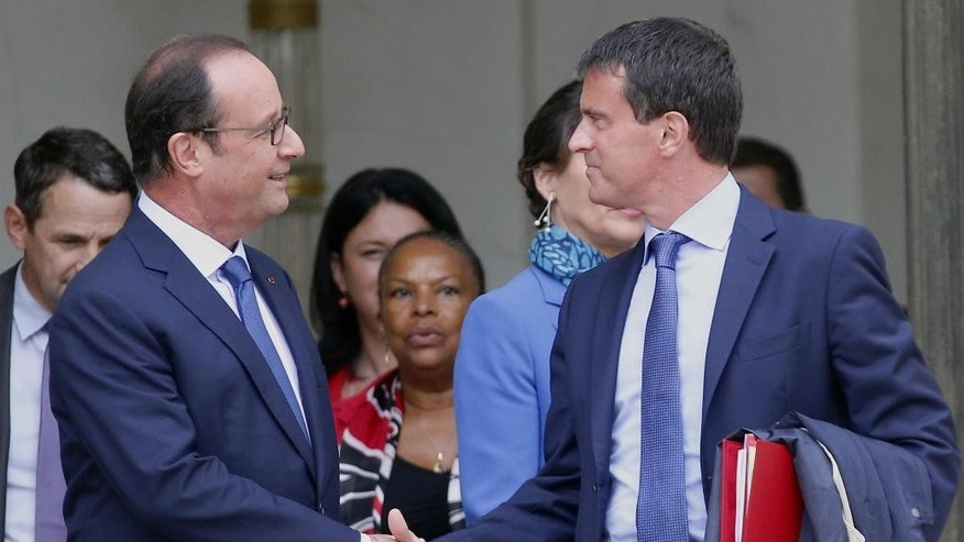 French President Francois Hollande, left, and  French Prime Minister Manuel Valls shake hands as they leave after the weekly cabinet meeting in Paris, France, Wednesday, Aug. 27, 2014. France's prime minister reshuffled his Cabinet on Tuesday to silence ministers who had openly criticized Socialist President Francois Hollande's economic policies as he tries to pull the nation out of stagnation and steer it toward growth. (AP Photo/Christophe Ena)