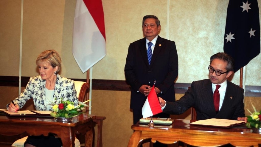 Indonesia's President Susilo Bambang Yudhoyono, center, witnesses Indonesia's Foreign Minister Marty Natalegawa, right, and Australia's Foreign Minister Julie Bishop sign the documents in Bali, Indonesia, Thursday, Aug. 28, 2014. Australia and Indonesia have reached a new agreement on how they'll use their intelligence operations in the future, even settling their disagreement on its name.(AP Photo/Firdia Lisnawati)