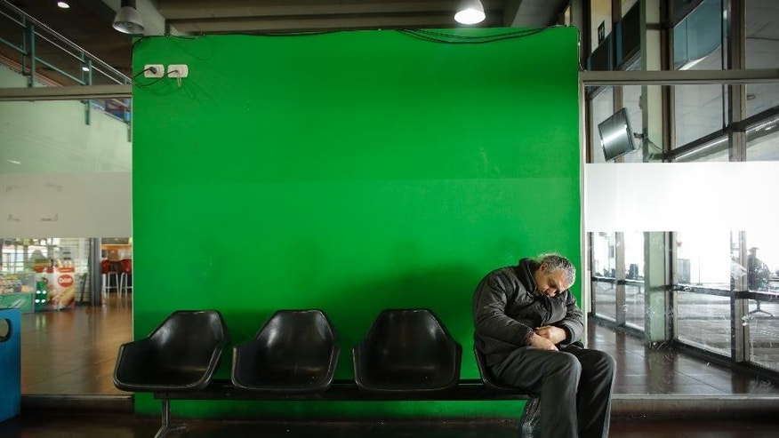 A man naps at a nearly empty long-distance bus station during a strike that is blocking roads throughout the city, affecting bus services in Buenos Aires, Argentina, Thursday, Aug. 28, 2014. Truck drivers, restaurant workers and some members of education unions joined a 24-hour walkout on Thursday, as a more radical opposition labor union continued their 36-hour strike that started Wednesday. The protests over taxes, wages and the overall cost of living in the country, come amid deepening economic troubles for Argentina, with the economy in recession and inflation running around 40 percent. (AP Photo/Victor R. Caivano)
