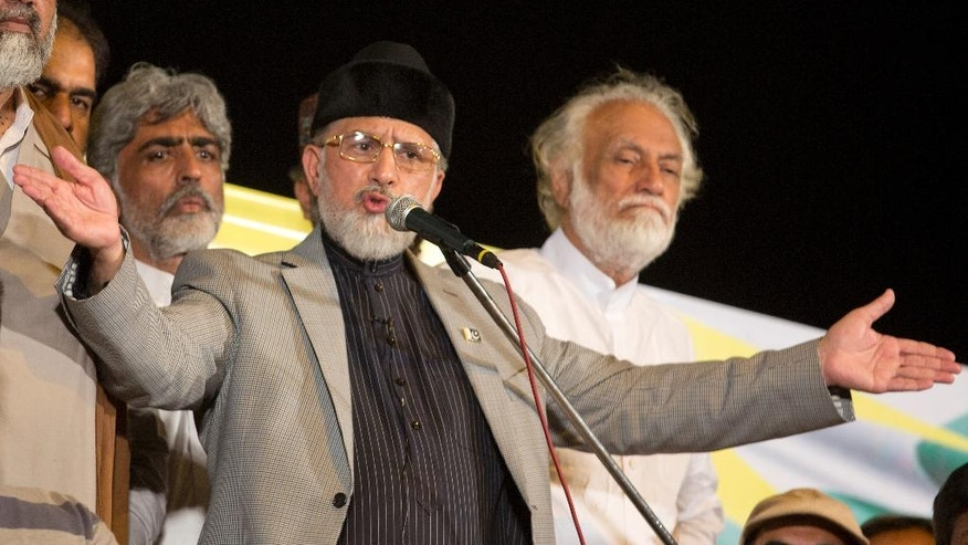 Pakistan's Muslim cleric Tahir-ul-Qadri announces the failure of negotiations with the government, in Islamabad, Pakistan, Wednesday, Aug. 27, 2014. A Cabinet minister on Wednesday urged Pakistan's two key opposition figures leading mass rallies outside parliament to back off their demand for the prime minister's resignation in ongoing talks with the government. The call by Railways Minister Saad Rafiq came as authorities and the two opposition leaders — cricket-star-turned-politician Imran Khan and fiery cleric Tahir-ul-Qadri — were set to continue negotiations later Wednesday. (AP Photo/B.K. Bangash)