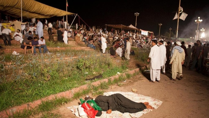 A supporter of Imran Khan, leader of Pakistan Tehrik-e-Insaf, takes a nap during sit-in-protest, Wednesday, Aug. 27, 2014 in Islamabad, Pakistan. A Cabinet minister on Wednesday urged Pakistan's two key opposition figures leading mass rallies outside parliament to back off their demand for the prime minister's resignation in ongoing talks with the government. The call by Railways Minister Saad Rafiq came as authorities and the two opposition leaders — cricket-star-turned-politician Imran Khan and fiery cleric Tahir-ul-Qadri — were set to continue negotiations later Wednesday. (AP Photo/B.K. Bangash)