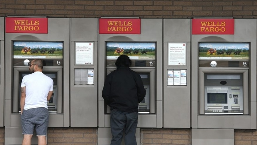 Customers use ATMs at a Wells Fargo Bank branch office on July 12, 2012 in Daly City, California. (Photo by Justin Sullivan/Getty Images)