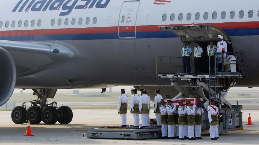 Malaysian Army soldiers carry a coffin containing the body of Mohd Ghafar Abu Bakar, a Malaysia Airlines in-flight supervisor who was among the victims on board Flight MH17, upon arrival at Kuala Lumpur International Airport in Sepang, Malaysia, Sunday, Aug. 24, 2014. (AP Photo/Lai Seng Sin)