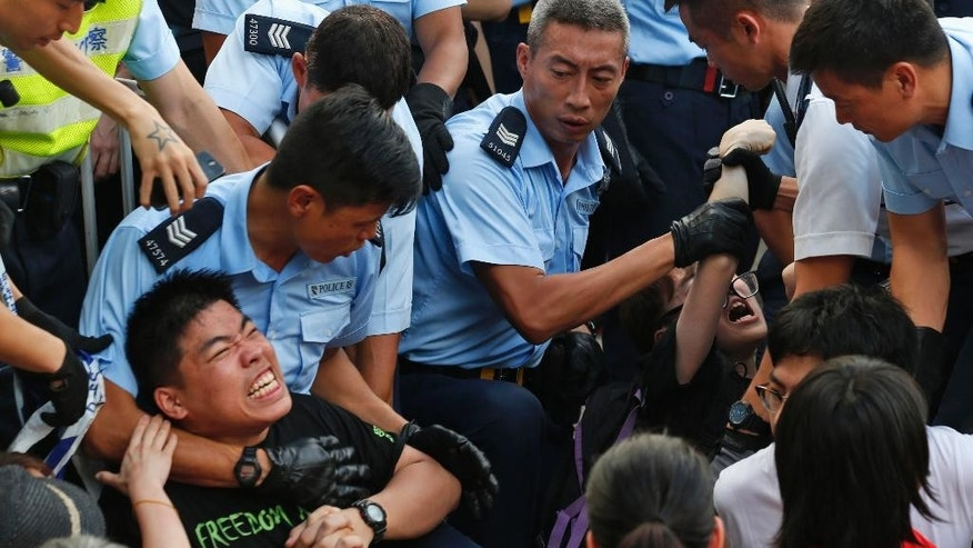 In this July 2, 2014 photo, protesters are taken away by police officers after hundreds of protesters staged a peaceful sit-ins overnight on a street in the financial district in Hong Kong. Hong Kong's simmering summer of discontent gets even hotter on Sunday, Aug. 31, 2014 when Beijing is expected to recommend restricting the first direct elections for the Chinese-controlled financial hub's leader, stepping up chances of a showdown with democracy groups. (AP Photo/Kin Cheung)