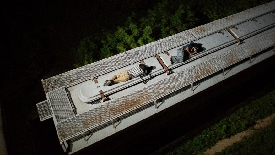 "In this Aug. 26, 2014 photo, Central American migrants sleep atop a moving freight train as it heads north from Arriaga toward Chahuites, Mexico. A Mexican crackdown seems to be keeping women and children off the deadly train, known as ""The Beast,"" that has traditionally helped thousands of migrants head north. The once-open route to the United States has become so difficult that trains now carry a small fraction of the migrants they used to, and almost exclusively adult men. (AP Photo/Rebecca Blackwell)"