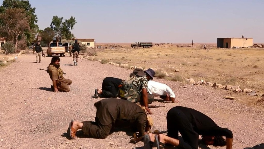 This undated image posted  Wednesday, Aug. 27, 2014 by the Raqqa Media Center of the Islamic State group, a Syrian opposition group, which has been verified and is consistent with other AP reporting, shows fighters from the Islamic State group that captured the Tabqa air base from the Syrian government on Sunday, praying inside the air base, in Raqqa, Syria.  A U.N. commission on Wednesday accused the extremist Islamic State organization of committing crimes against humanity with attacks on civilians, as pictures emerged of the extremists' bloody takeover of a Syrian military air base that added to the international organization's claims.  (AP Photo/ Raqqa Media Center of the Islamic State group)