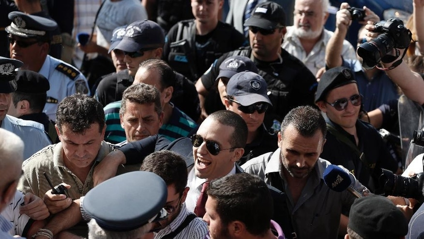 Parliament member Ilias Kasidiaris, centre, escorted by police officers, arrives to a municipal amphitheater where center-left Mayor Giorgos Kaminis was sworn in for a second five-year term in Athens, on Friday, Aug. 29, 2014. Jailed spokesman of Greece's extreme right Golden Party Kasidiaris has been granted a brief leave from prison to take up his seat on Athens' new city council, after the party won 16 percent of the capital's vote in May municipal elections. Golden Dawn, an ultranationalist party of Neo-Nazi origins, has seen its support soar during Greece's financial crisis. Nine of its 18 lawmakers are currently in prison, awaiting trial for alleged criminal activity. (AP Photo/Petros Giannakouris)