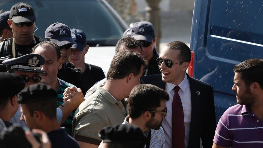 Parliament member Ilias Kasidiaris, second right, escorted by police officers, arrives to a municipal amphitheater where center-left Mayor Giorgos Kaminis was sworn in for a second five-year term in Athens, on Friday, Aug. 29, 2014. Jailed spokesman of Greece's extreme right Golden Party Kasidiaris has been granted a brief leave from prison to take up his seat on Athens' new city council, after the party won 16 percent of the capital's vote in May municipal elections. Golden Dawn, an ultranationalist party of Neo-Nazi origins, has seen its support soar during Greece's financial crisis. Nine of its 18 lawmakers are currently in prison, awaiting trial for alleged criminal activity. (AP Photo/Petros Giannakouris)
