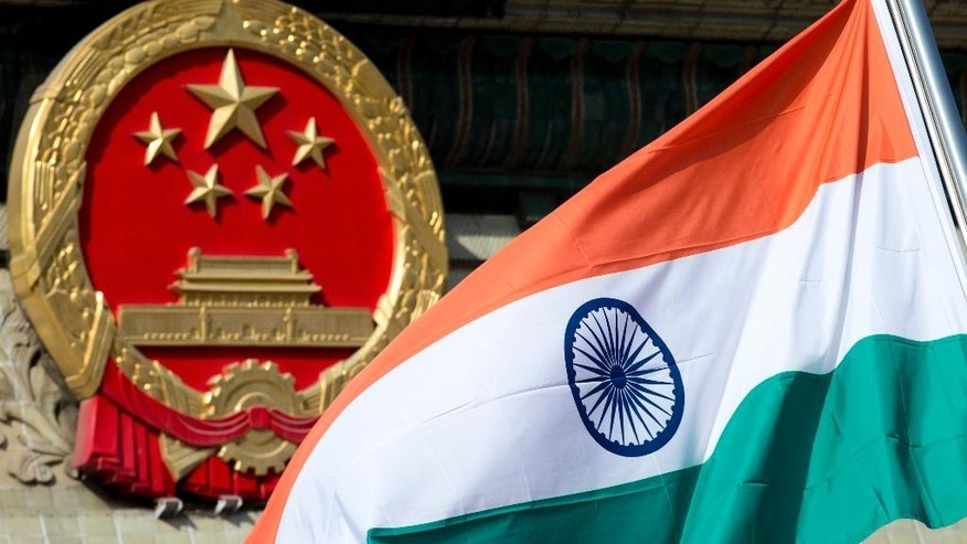 FILE - In this Oct. 23, 2013 file photo, an Indian national flag is flown next to the Chinese national emblem during a welcome ceremony for visiting then Indian Prime Minister Manmohan Singh, outside the Great Hall of the People in Beijing. For more than 50 years, it has pitted India against China _ a smoldering dispute over who should control a swath of land larger than Austria. Two militaries have skirmished. A brief, bloody war has been fought. And today, thousands of soldiers from both countries sit deployed along their shared frontier, doing little but watching each other.  (AP Photo/Andy Wong, file)