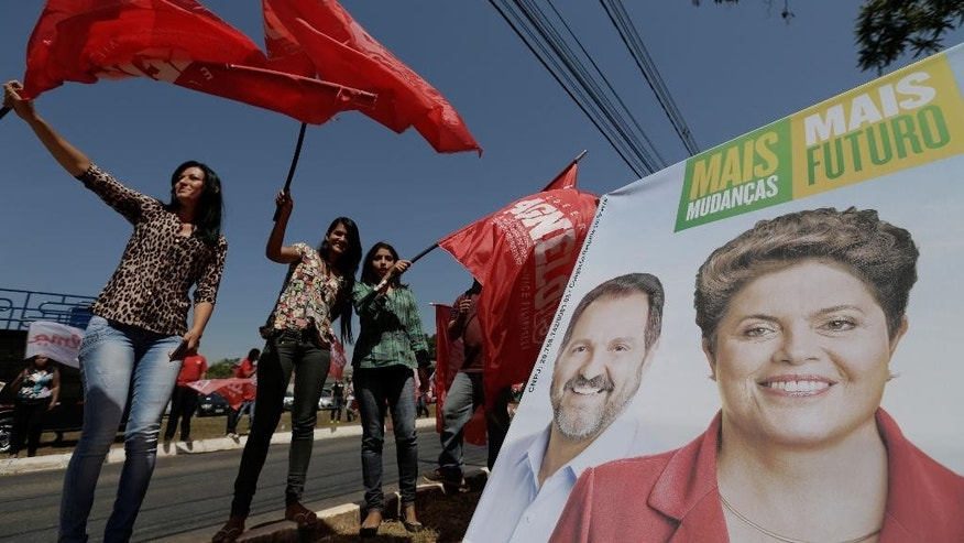 Supporters wave campaign flags of Brazil's President Dilma Rousseff, who is running for reelection with the Workers Party (PT), before a campaign rally at the Confederation of Agricultural Workers headquarters in Brasilia, Brazil, Thursday, Aug. 28, 2014. Brazil's presidential election is scheduled for Oct. 5, 2014. (AP Photo/Eraldo Peres)