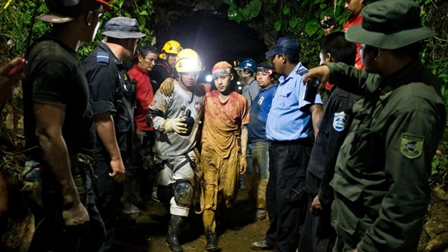 Leber Vivas Gonzales, 16, center right, is accompanied by a rescue worker as he leaves on his own feet the entrance to the El Comal gold and silver mine in Bonanza, Nicaragua, Friday, Aug. 29, 2014.  The first 11 of 24 freelance gold miners trapped by a collapse in a mine have been rescued and crews were working early Saturday to free more, officials said. (AP Photo/Esteban Felix)
