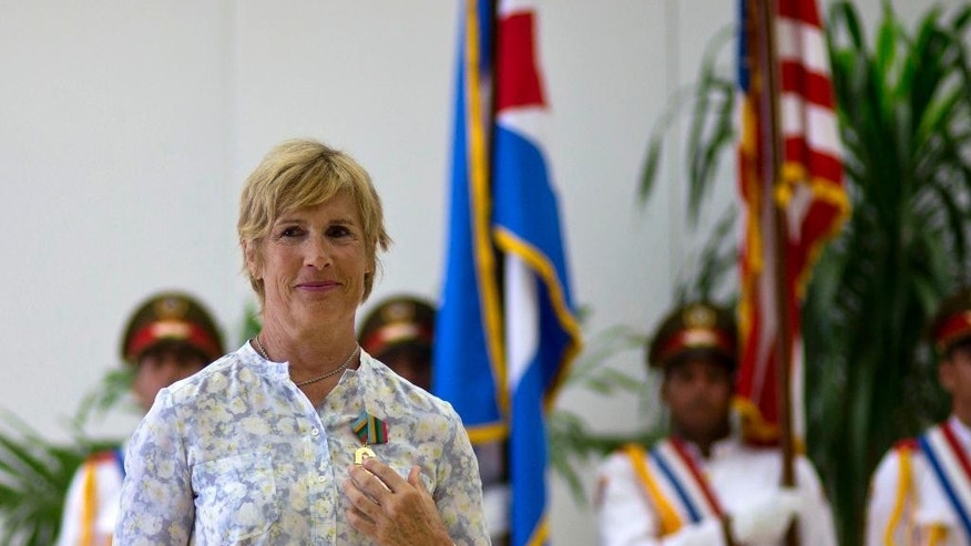 U.S. endurance swimmer Diana Nyad wears her Order of Sporting Merit medal as she stands in front of the Cuban and U.S. flags during a ceremony in Havana, Cuba, Saturday, Aug. 30, 2014. Cuba honored Nyad for being the first swimmer to make the crossing between Cuba and Florida without flippers or a shark cage for protection. Nyad made four previous attempts; first in 1978, and three times in 2011 and 2012. (AP Photo/Ramon Espinosa)