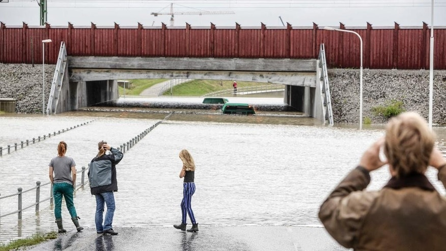 Two buses are partly visible above water under an overpass in Malmo, southern Sweden, Sunday Aug. 31, 2014. Heavy rains and flash floods have snarled road and rail traffic in Sweden and Denmark, with divers called to rescue some people in submerged vehicles. Overnight rains which spread into Sunday forced the evacuation of residents to be evacuated from waterlogged homes in some areas. Buses in the Swedish city of Malmo came to halt after vehicles broke down on flooded roads with divers helping to evacuate passengers from submerged vehicles. (AP photo/Stig-Ake Jonsson, TT News Agency)    SWEDEN OUT