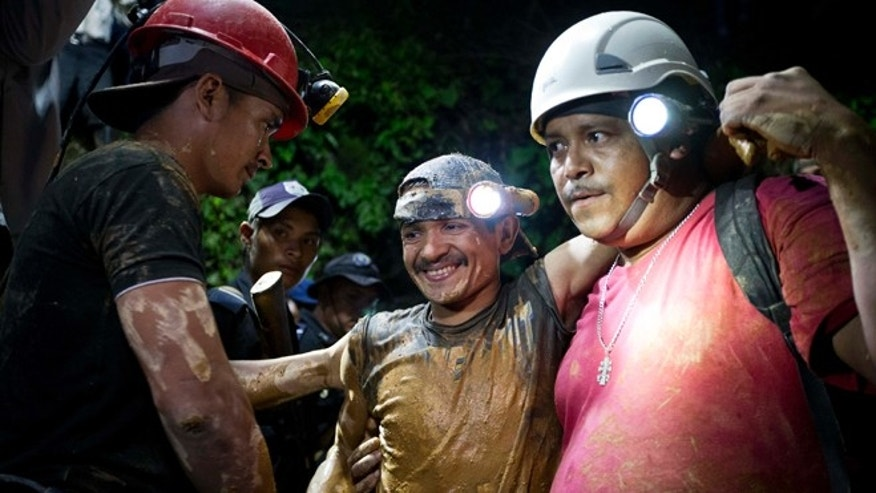 Aug. 29, 2014: A rescued miner, center, is greeted by another miner while being helped by a rescue worker as he leaves the El Comal gold and silver mine in Bonanza, Nicaragua. (AP)
