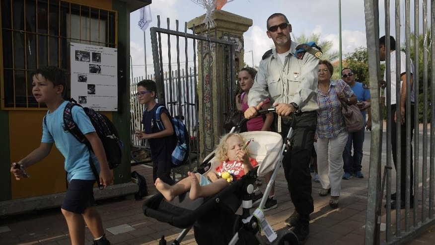 Israeli students with their parents make their way to elementary school on the first day of the school year in the costal city of Ashkelon, Monday, Sept. 1, 2014. Thousands of children in southern Israel return to school Monday after spending the summer vacation in bomb shelters taking cover from the thousands of Palestinian rockets and mortars fired from Gaza during 50 days of war. (AP Photo/Tsafrir Abayov)