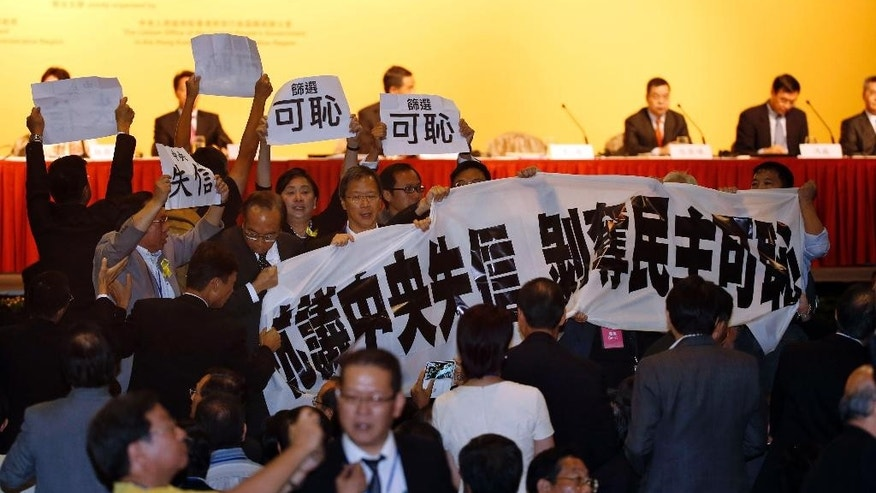 "A security guard, bottom left, tries to stop pro-democracy lawmakers protesting against Li Fei, deputy secretary general of the National People's Congress' Standing Committee, during a briefing session in Hong Kong Monday, Sept. 1, 2014. China's legislature on Sunday ruled out allowing open nominations in the inaugural election for Hong Kong's leader, saying they would create a ""chaotic society."" Democracy activists in the Asian financial hub responded by saying that a long-threatened mass occupation of the heart of the city ""will definitely happen."" The banner reads ""Protest against Central government breaking a promise, shame on deprivation of democracy."" (AP Photo/Kin Cheung)"