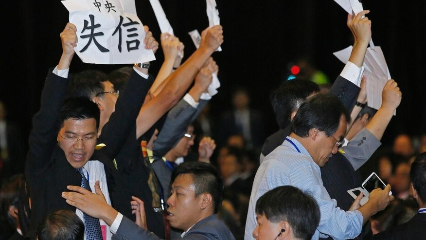 "Pro-democracy lawmaker Gary Fan Kwok-wai, left, raises a placard which reads "" Central Government break the promise "" and other lawmakers protest against Li Fei, deputy secretary general of the National People's Congress' Standing Committee, during a briefing session in Hong Kong Monday, Sept. 1, 2014. China's legislature on Sunday ruled out allowing open nominations in the inaugural election for Hong Kong's leader, saying they would create a ""chaotic society."" Democracy activists in the Asian financial hub responded by saying that a long-threatened mass occupation of the heart of the city ""will definitely happen."" (AP Photo/Vincent Yu)"