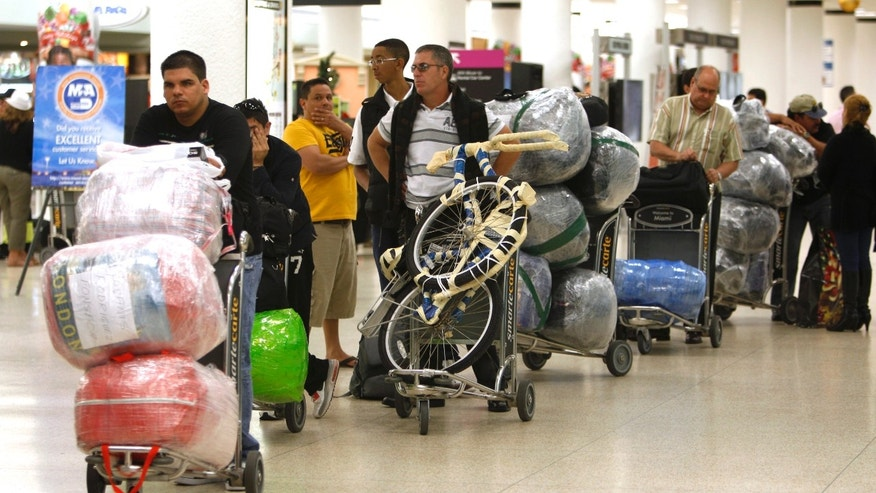 Travelers wait in line with their luggage at Miami International Airport before traveling Cuba in Miami. The Cuban government has enacted new rules sharply limiting the amount of goods people can bring into Cuba in their luggage, and ship by boat from abroad. (AP Photo/Lynne Sladky, File)