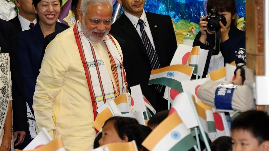 Indian Prime Minister Narendra Modi is welcomed as he visits Taimei Elementary School in Tokyo, Monday, Sept. 1, 2014. (AP Photo/Koji Sasahara)