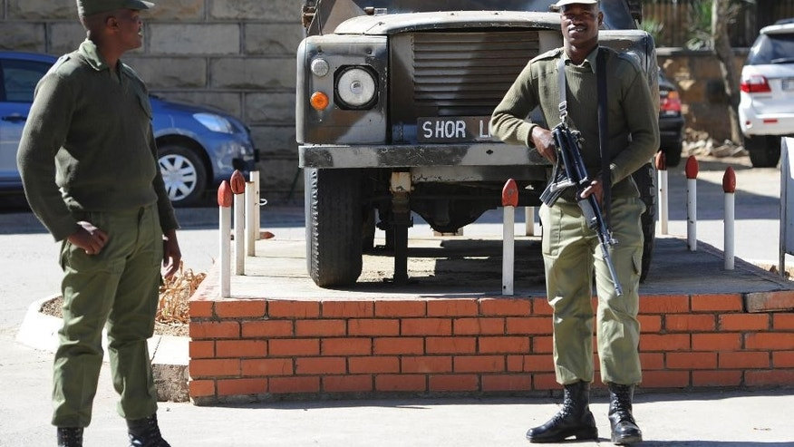 In this  Sunday,  Aug. 31, 2014 photo, army personnel man outside the military headquarters in Maseru, Lesotho.  Lesotho's prime minister fled to South Africa in fear for his safety and will now meet with leaders of the region there to seek peace, he said Sunday. Prime Minister Thomas Thabane said there had been an attempt to take over Lesotho, a country of about 2 million people that is surrounded by South Africa. Lesotho's Defense Forces deny any attempt at a coup although they say the military exchanged gunfire and disarmed two police stations in Lesotho's capital, Maseru, on Saturday. (AP Photo)