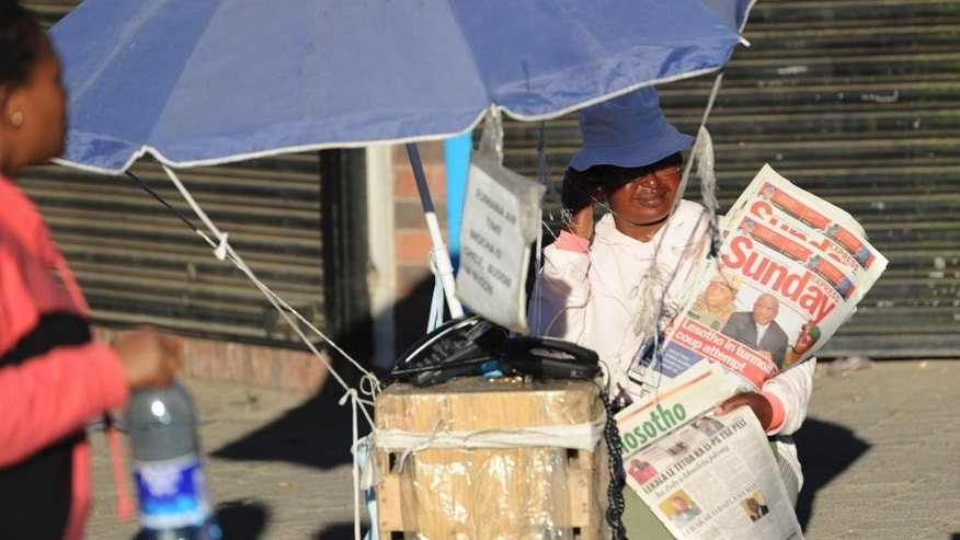 "In this  Sunday Aug. 31, 2014 photo, a vendor sells newspapers headlined ""Lesotho in turmoil coup attempt"" in Maseru, Lesotho. Lesotho's prime minister fled to South Africa in fear for his safety and will now meet with leaders of the region there to seek peace, he said Sunday. Prime Minister Thomas Thabane said there had been an attempt to take over Lesotho, a country of about 2 million people that is surrounded by South Africa. Lesotho's Defense Forces deny any attempt at a coup although they say the military exchanged gunfire and disarmed two police stations in Lesotho's capital, Maseru, on Saturday. (AP Photo)"