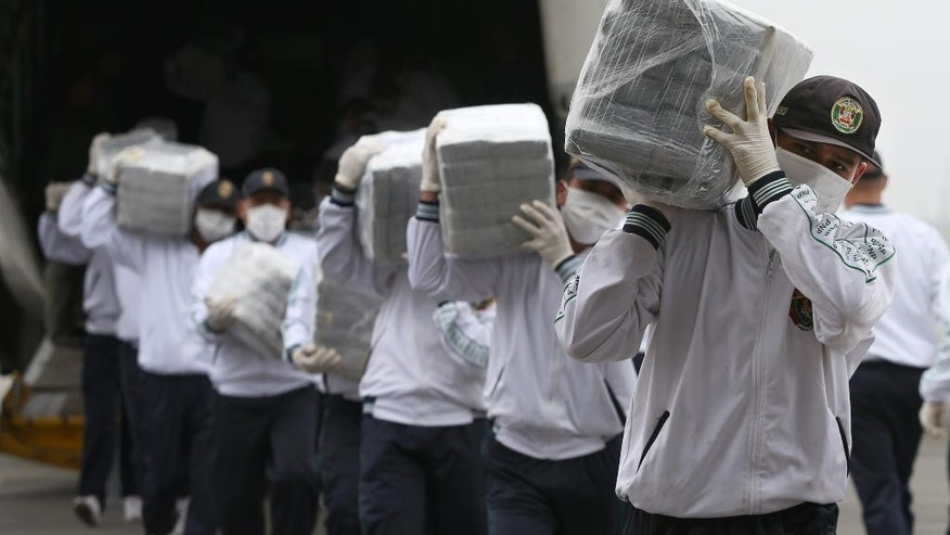 Police carry blocks of seized cocaine as they present it to the press at a police base in Lima, Peru, Monday, Sept. 1, 2014. Police announced that they seized 7.7 metric tons (8.5 tons) of cocaine in the northern town of Trujillo on Aug. 26, and that it's the largest seizure of cocaine in Peru's history. (AP Photo/Martin Mejia)