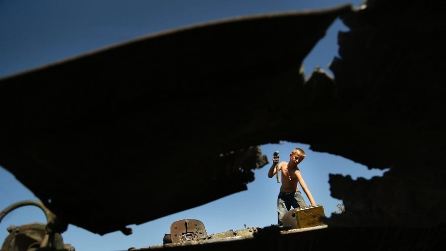 Denis Bespalko, 9, loosens parts from a burned-out Ukrainian armored personnel carrier in the village of Hrabske, eastern Ukraine, Sunday, Aug. 31, 2014. The fight for Ilovaisk and surrounding areas, including the village of Hrabske, between Ukrainian government troops and pro-Russian separatist fighters was bitter and lasted the best part of a month. (AP Photo/Sergei Grits)