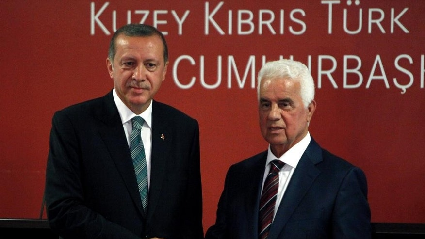Turkey's new President Recep Tayyip Erdogan, left, and Turkish Cypriot leader Dervis Eroglu shake hands after a press conference and their meeting in the breakaway Turkish Cypriot north of ethnically divided Cyprus on Monday, Sept. 1, 2014. This is Erdogan's first visit abroad since his election last month. Cyprus was divided in 1974 when Turkey invaded after a coup by supporters of union with Greece. (AP Photo/Petros Karadjias)