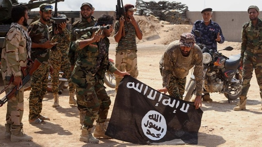 September 1, 2014: Iraqi security forces hold a flag of the Islamic State group they captured during an operation outside Amirli, some 105 miles north of Baghdad. (AP Photo)