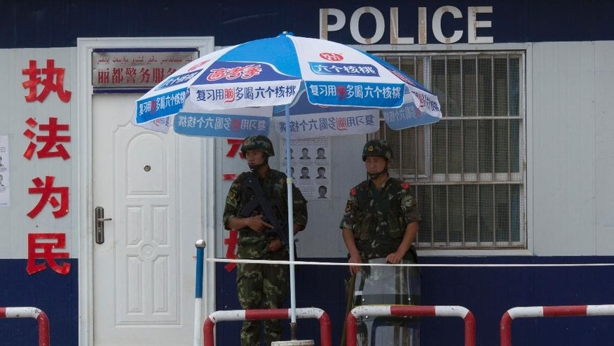 In this photo taken Thursday, July 17, 2014, Chinese paramilitary policemen stand on duty in front of a wanted poster in the city of Aksu in western China's Xinjiang province.  China has blanketed parts of Xinjiang, home to Muslim, Turkic-speaking Uighurs, with such heavy security that it resembles an occupied territory under martial law, complete with armed troops, spiked barricades, checkpoints and even drones. But the massive security effort has not brought stability to Xinjiang, and neither has Beijing's strategy of pouring in economic investment. A few hundred people have died in ethnic violence in Xinjiang and in two attacks in Chinese cities elsewhere over the past 16 months.  (AP Photo/Ng Han Guan)
