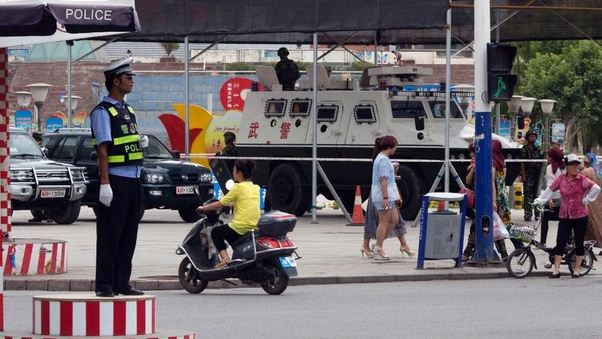 In this photo taken Thursday, July 17, 2014, a Chinese paramilitary armored vehicle is parked at a major intersection in the city of Aksu in western China's Xinjiang province.  China has blanketed parts of Xinjiang, home to Muslim, Turkic-speaking Uighurs, with such heavy security that it resembles an occupied territory under martial law, complete with armed troops, spiked barricades, checkpoints and even drones. But the massive security effort has not brought stability to Xinjiang, and neither has Beijing's strategy of pouring in economic investment. A few hundred people have died in ethnic violence in Xinjiang and in two attacks in Chinese cities elsewhere over the past 16 months.  (AP Photo/Ng Han Guan)