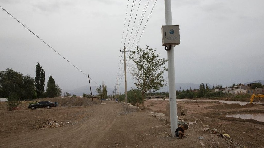 In this photo taken Wednesday, July 16, 2014, a child plays under police surveillance cameras set up to monitor a dirt road intersection in Kuqa in western China's Xinjiang province. China has blanketed parts of Xinjiang, home to Muslim, Turkic-speaking Uighurs, with such heavy security that it resembles an occupied territory under martial law, complete with armed troops, spiked barricades, checkpoints and even drones. But the massive security effort has not brought stability to Xinjiang, and neither has Beijing's strategy of pouring in economic investment. A few hundred people have died in ethnic violence in Xinjiang and in two attacks in Chinese cities elsewhere over the past 16 months.  (AP Photo/Ng Han Guan)