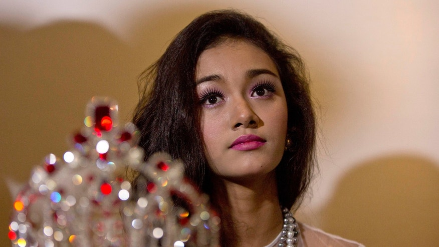 Sept. 2, 1014: May Myat Noe, Myanmar's first international beauty queen, winner of the 2014 Miss Asia Pacific World, sits with her crown that she allegedly ran away with, during a press conference in Yangon, Myanmar. (AP/Gemunu Amarasinghe)