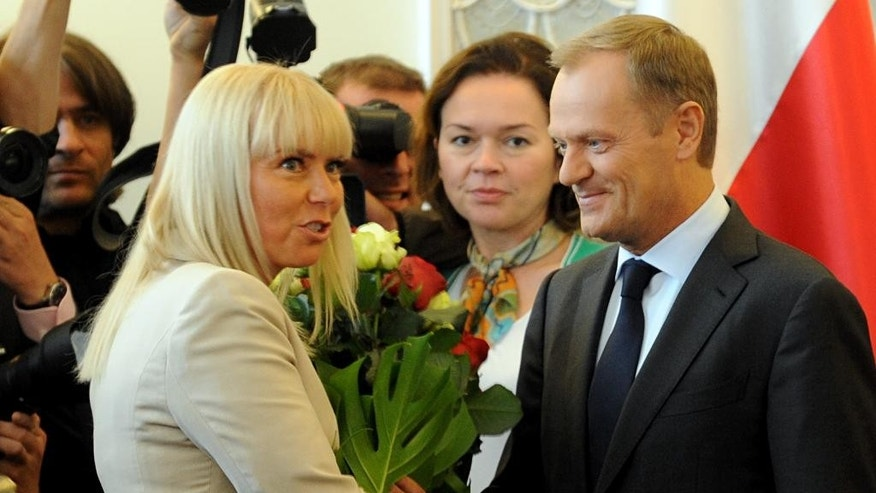 Polish Prime Minister Donald Tusk, right, receives flowers from Deputy Prime Minister Elzbieta Bienkowska as he arrives for a government meeting in Warsaw, Poland, Tuesday, Sept. 2, 2014. Tusk was chosen by European leaders to be the next president of the European Council.   (AP Photo/Alik Keplicz)
