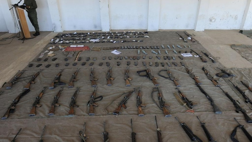 A Lesotho Defence Force member displays arms and ammunition confiscated from police at army barracks in Maseru, Lesotho, Monday, Sept. 1, 2014. Southern Africa's regional body said Monday it will send an envoy and an observer team to Lesotho to help restore stability and security in the mountainous kingdom where military actions over the weekend caused the prime minister to flee. (AP Photo)