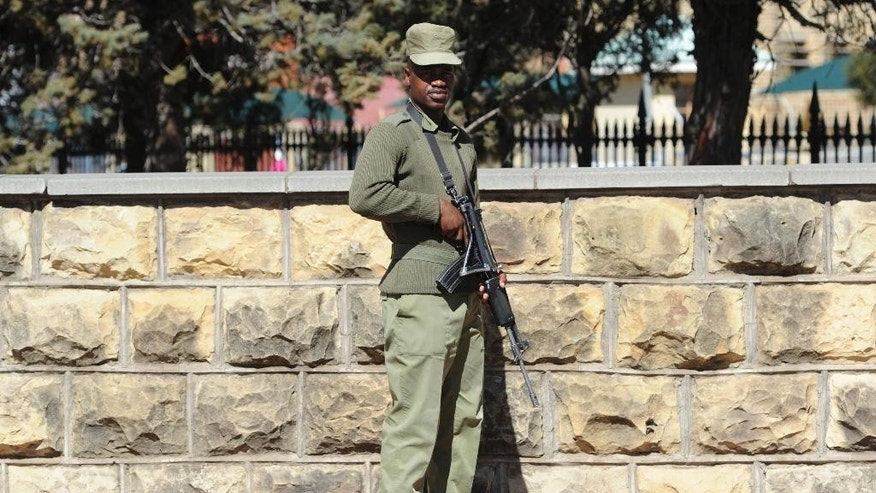 In THIS , Sunday Aug. 31, 2014 photo, an armed soldier stands outside the military headquarters in Maseru, Lesotho. Lesotho's prime minister fled to South Africa in fear for his safety and will now meet with leaders of the region there to seek peace, he said Sunday. Prime Minister Thomas Thabane said there had been an attempt to take over Lesotho, a country of about 2 million people that is surrounded by South Africa. Lesotho's Defense Forces deny any attempt at a coup although they say the military exchanged gunfire and disarmed two police stations in Lesotho's capital, Maseru, on Saturday.  (AP Photo)