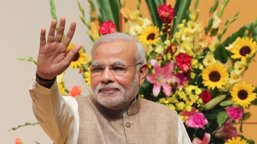 Indian Prime Minister Narendra Modi waves after his lecture at the University of the Sacred Heart in Tokyo, Tuesday, Sept. 2, 2014. Modi is currently on a five-day visit to Japan. (AP Photo/Koji Sasahara)