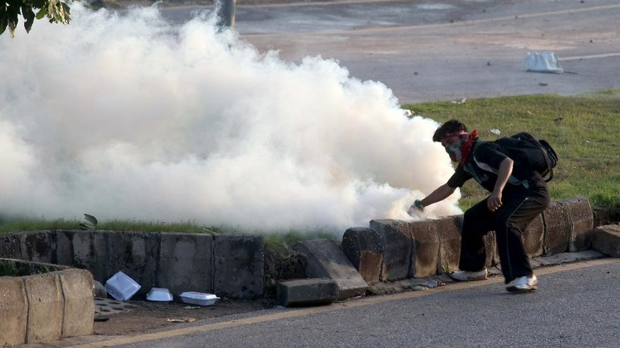 A Pakistani protester picks up a tear gas canister to throw back towards police during a clash in Islamabad, Pakistan, Monday, Sept. 1, 2014. Anti-government protesters stormed Pakistan's state television building Monday, forcing the channel briefly off the air as they clashed with police and pushed closer to the prime minister's residence. The violence comes as part of the mass demonstrations led by cleric Tahir-ul-Qadri and opposition politician Imran Khan that demand Prime Minister Nawaz Sharif resign. (AP Photo/Anjum Naveed)