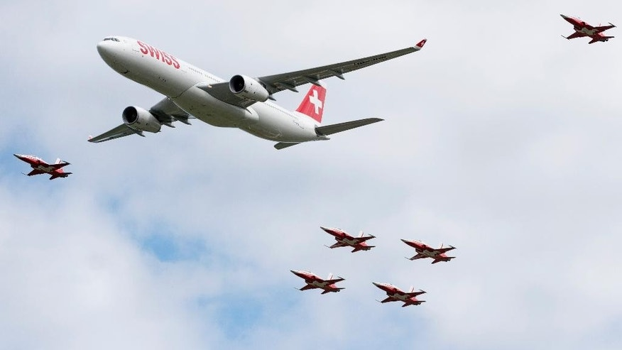 Escorted by six Tiger F5-E jets an Swiss airline Airbus A330 flies above  the spectators of an  air show in Payerne, Switzerland, Saturday, Aug.  30, 2014. Swiss air force celebrate it's 100.  bicentenary with a big air show.  (AP Photo/Keystone,Alessandro della Valle)