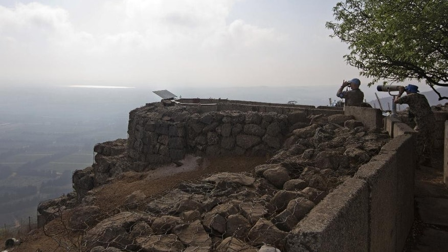 U.N. soldiers observe Syria's Quneitra province at an observation point on Mount Bental in the Israeli-controlled Golan Heights, overlooking the border with Syria, Monday, Sept. 1, 2014. (AP Photo/Sebastian Scheiner)