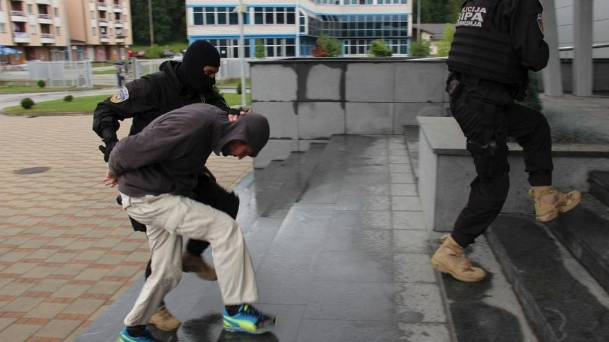 Bosnian police officers  escort  man who was detained  during action in the Bosnian capital of Sarajevo, on Wednesday, Sept. 3, 2014. Bosnian police say they have detained 15 people suspected of having fought in Syria and Iraq or of recruiting and funding other Balkan men to join the Islamic militants there. (AP Photo/Amel Emric)