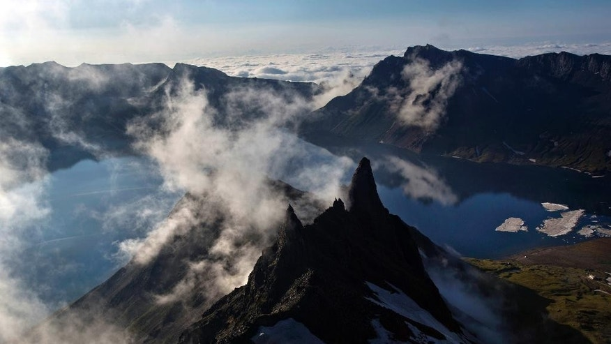 In this Wednesday, June 18, 2014 photo, clouds float over the peak of Mt. Paektu in North Korea's Ryanggang province. More than a thousand years ago, a huge volcano straddling the border between North Korea and China was the site of one of the biggest eruptions in human history, blanketing eastern Asia in its ash. But unlike other major volcanos around the world, the remote and politically sensitive Mount Paektu remains almost a complete mystery to foreign scientists who have - until recently - been unable to conduct on-site studies. (AP Photo/David Guttenfelder)